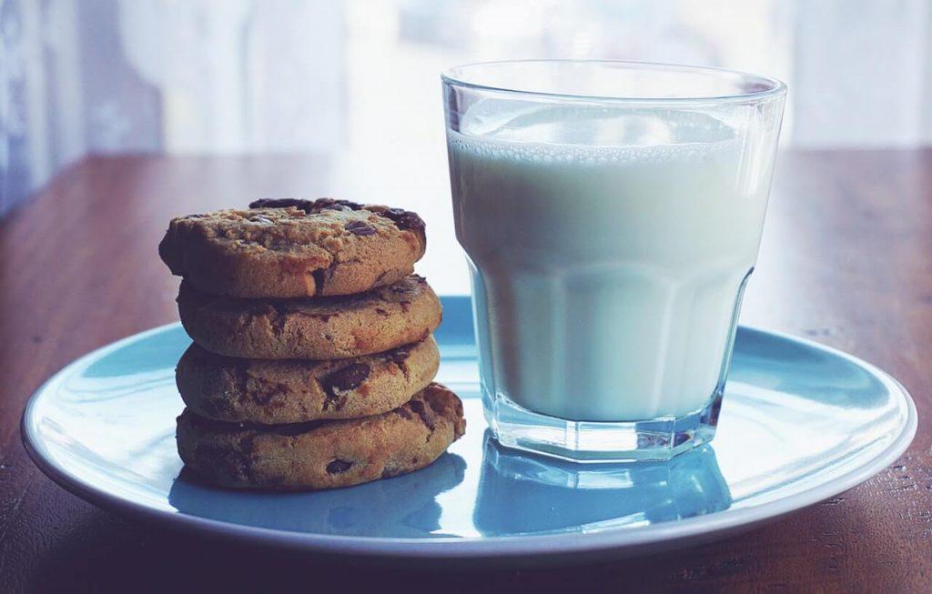 glas melk met koekjes op een bord