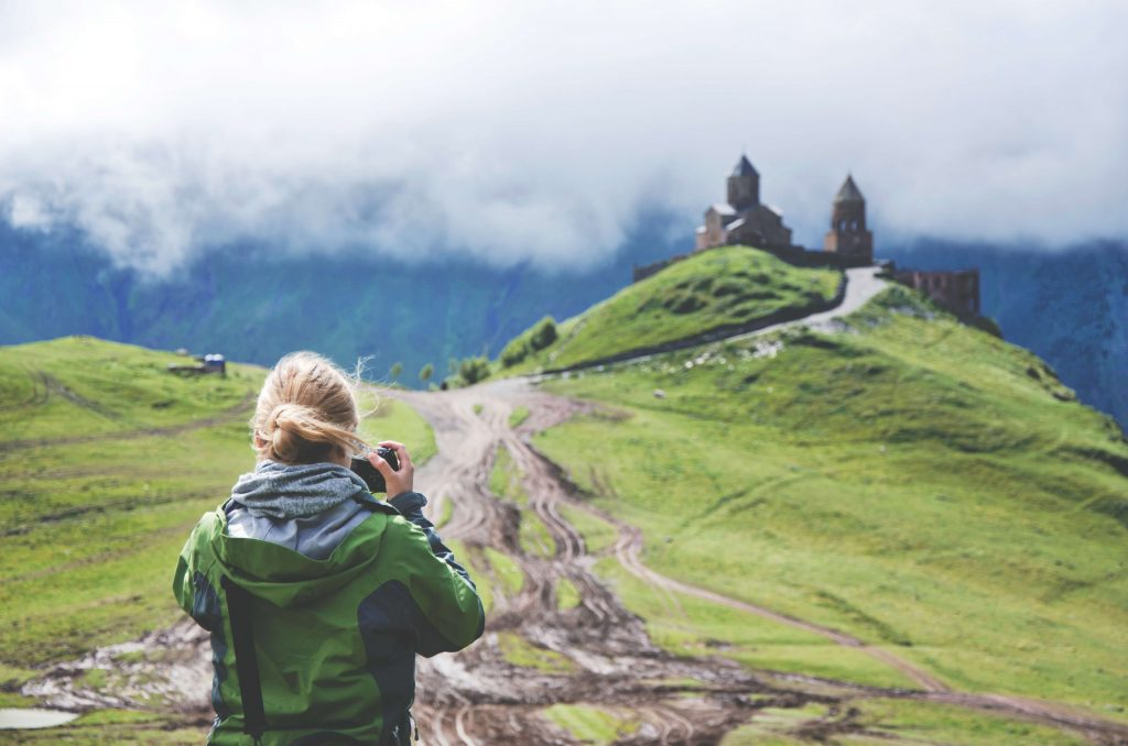 meisje met groene jas voor groene natuur maakt een foto
