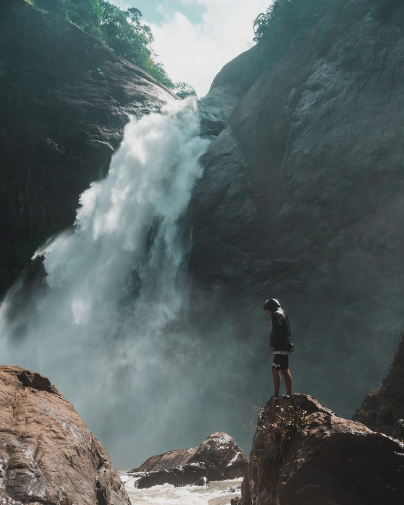 man voor een waterval in de natuur