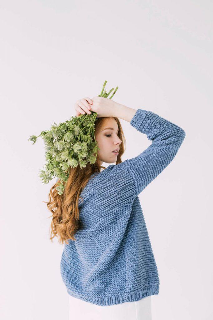 meisje met dik vest en planten in haar hand